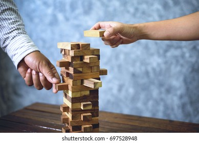 Businessmen are playing jenga game. concept of doing business is always risky, requires strategic management.