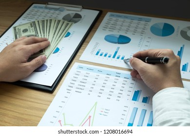 Businessmen are pointing numbers, graph, chart in business results. Business concept.