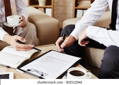 Businessmen pointing at text of contract while discussing it
