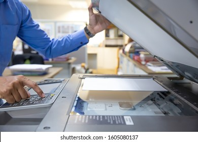 Businessmen press button on the panel of photocopier or printer for printout, scanning, exrox documents papers at office workplace.