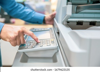 Businessmen press button on the panel for using photocopier or printer for printout and scanning document paper at office.