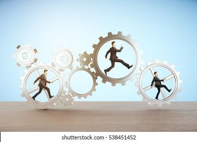 Businessmen running inside cogwheels on blue background. 3D Rendering. Teamwork concept