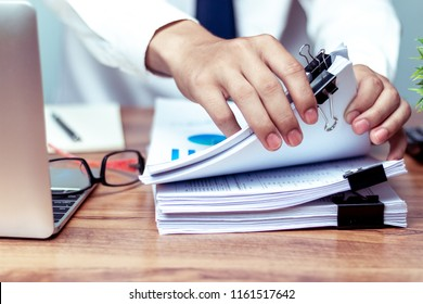 Businessmen are searching for documents lying on the table,business report papers,important documents.