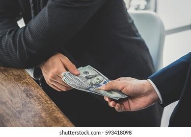 Businessmen secretly passing money - bribery and corruption concepts