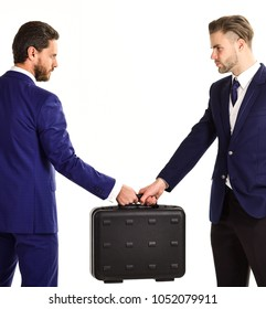 Businessmen with serious faces hold black briefcase. Business exchange concept. Handover of suitcase in hands of partners, isolated on white background. Business deal between businessmen in suits.