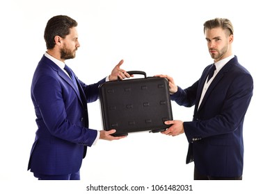 Businessmen with serious faces hold black briefcase. Handover of suitcase in hands of partners on white background. Business exchange between businessmen in classic suits. Business and deal concept.