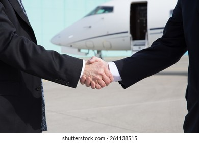 Businessmen shake hands in front of a corporate jet