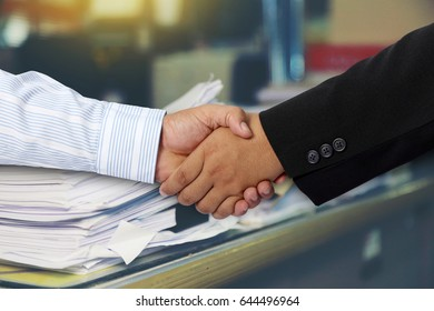 Businessmen shake hands and Paper documents stacked background.Concept business cooperation.
