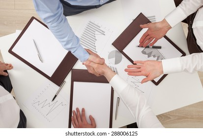 Businessmen shake hands, view from above