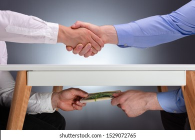 Businessmen Shaking Hands After The Business Deal Receiving A Bribe Money Under The Table