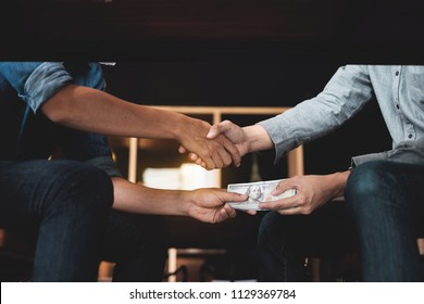 Businessmen shaking hands with bribe money under table. Corruption and Anti Bribery concepts.
