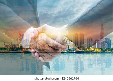 Businessmen are shaking hands for business venture and Marketing to invest in energy. The background is a large oil refinery. The work is ongoing.