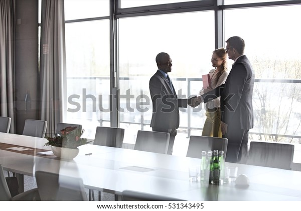 Businessmen shaking hands by female colleague in conference room at office