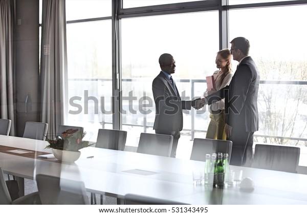 Biznesmeni uściskając ręce przez koleżankę w sali konferencyjnej w biurze