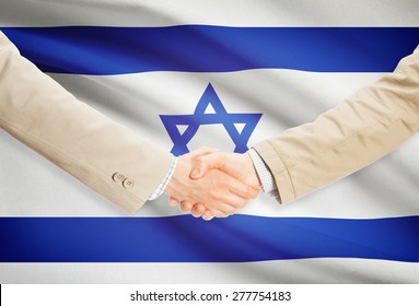Businessmen shaking hands with flag on background - Israel