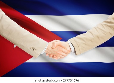 Businessmen shaking hands with flag on background - Cuba