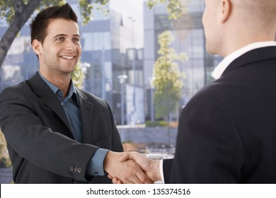 Businessmen shaking hands in front of office building, smiling.