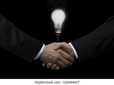 Businessmen Shaking Hands With Light Bulb