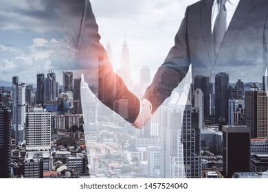 Businessmen shaking hands on blurry Kuala Lumpur city background. Teamwork and success concept. Multiexposure