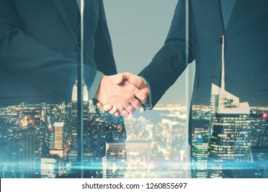Businessmen shaking hands on night city background. Teamwork and partnership concept. Double exposure