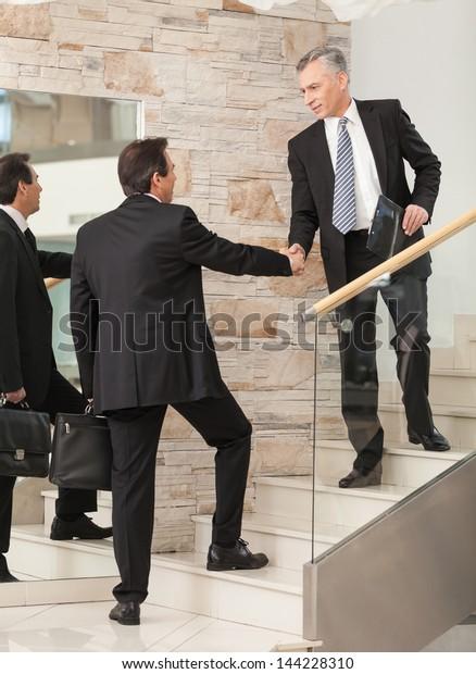 Businessmen shaking hands on steps before board meeting