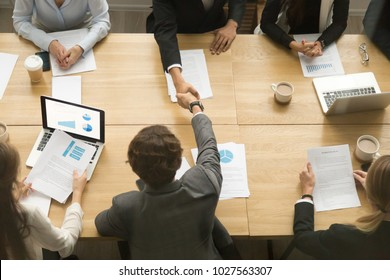 Businessmen shaking hands sitting at conference table during team meeting, two male entrepreneurs handshaking making deal starting collaboration at group negotiations teamwork, top view from above