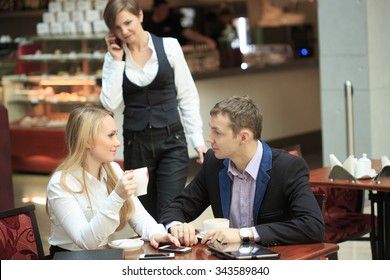 Businessmen sitting for a laptop, discussing plans.man and woman in cafe.