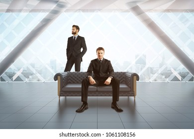 Businessmen sitting on sofa in modern concrete interior with city view. Teamwork concept. 3D Rendering
