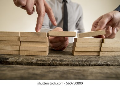 Businessmen solving problems by building bridges with wooden blocks to span a gap for partner to walk his fingers across in a conceptual image.