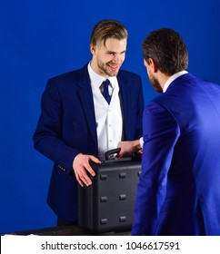 Businessmen speaking about transaction. Business deal concept. Men in suit or businessmen meet for handover of black briefcase. Business partners with smiling face on blue background.