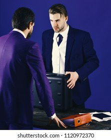 Businessmen speaking about transaction. Business handover concept. Men in suit or businessmen meet for handover of black briefcase and red folder. Business partners with strict face on blue background