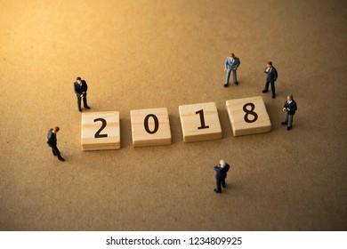 Businessmen standing around 2018 wood plate