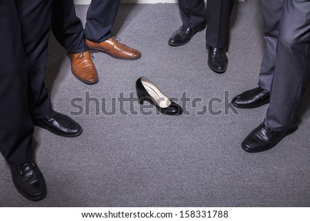 Businessmen standing in a circle around a woman's high heel