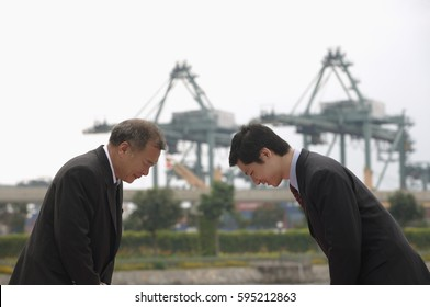 Businessmen standing face to face, bowing