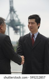 Businessmen standing face to face, shaking hands