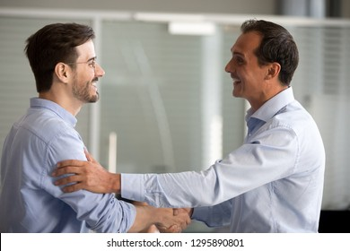 Businessmen standing smiling shaking hands greeting congratulating each other at business meeting. Millennial office workers handshaking during acquaintance expressing trust support and collaboration