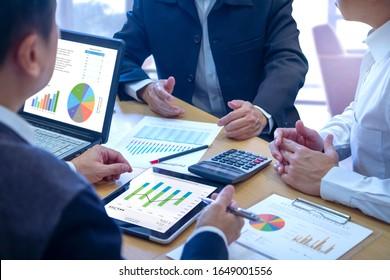 Ficha Empresarios en la pantalla táctil de tableta para revisar profundamente un diagrama o gráfico e informes financieros para un rendimiento sobre análisis de riesgo de inversión o de inversión o rendimiento del negocio.