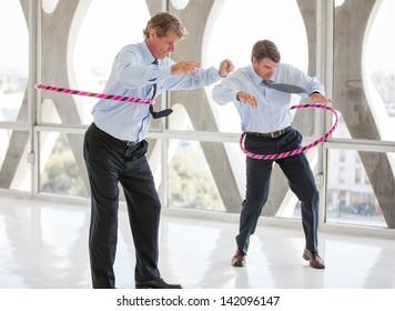 Businessmen taking a play Break hula hooping in a modern office to get ideas flowing