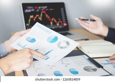 Businessmen talking about stock market invest trading online analysis discussing financial graph  for investment purposes discussion in traders office