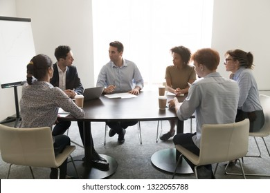 Businessmen talking discussing business project at multi ethnic board meeting in conference room, diverse people employees sit at negotiation table work together at corporate group office briefing