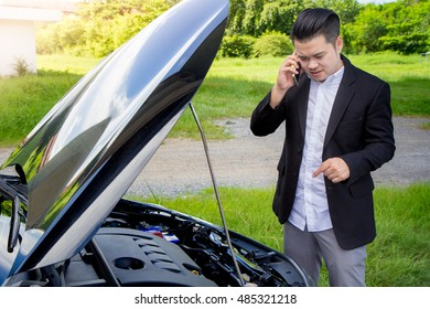 businessmen talking on a cell phone by a broken car On Country Road Phoning For Help, Man broken car.