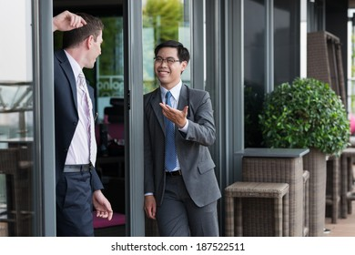 Businessmen talking while standing near office building entrance