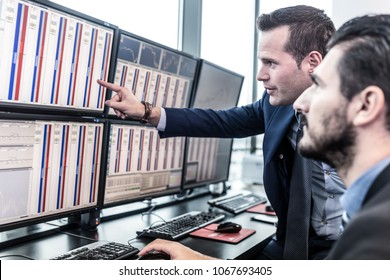 Businessmen trading stocks. Stock traders looking at charts, indexes and numbers on multiple computer screens. Colleagues in discussion in traders office. Broker pointing on market data on monitor.