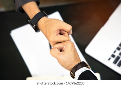 Businessmen trust commitment as  support which Business Partners holding hands relationship marketing for reach successful achievement and meeting commit concept