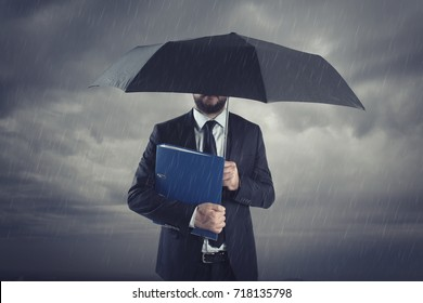 Businessmen with umbrella standing in stormy rain.Insurance agent and consultant in business crisis situation.