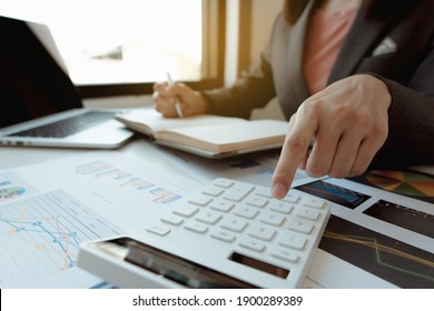 Businessmen use a calculator to calculate income and expenses in order to manage budgets to pay off credit card debt.