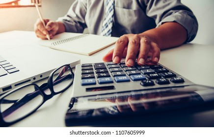 Businessmen are using a calculator to calculate the income of the business.