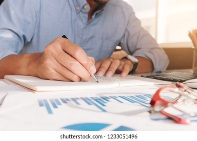 Businessmen using computer and calculator during note some data on notepad for calculate financial