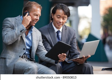 Businessmen using laptop and tablet pc while communication on cell phone