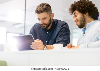 Businessmen using tablet computer in office